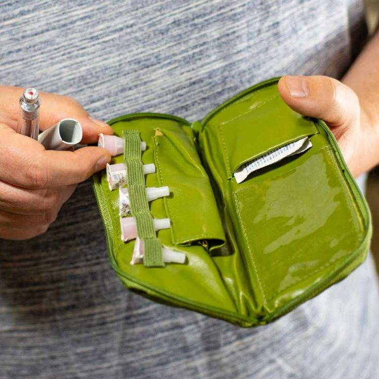 Man holding Green Dittibag open filled with insulin