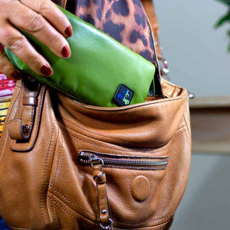 Woman putting Green Dittibag into purse