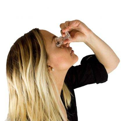 Woman using eye wash cup to clean her right eye.
