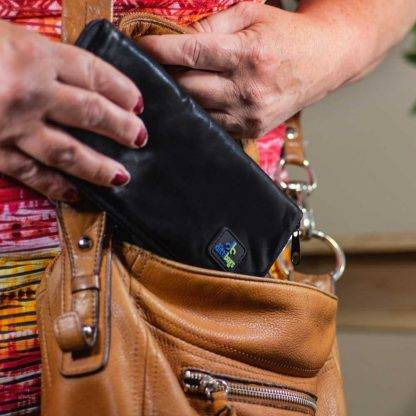 Woman putting Black Dittibag into purse