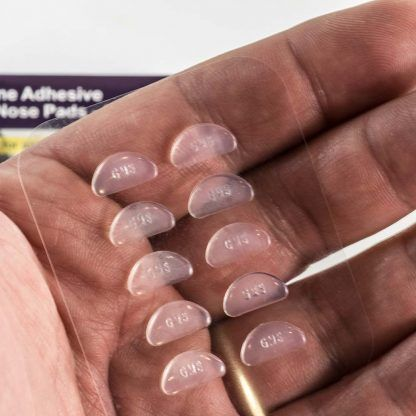 GMS Optical Contour Silicone Nose Pads - 13mm x 1.8mm Clear on person's hand