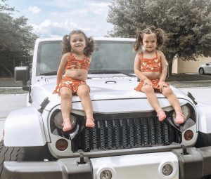 Aleah and Alana sitting on a jeep in swim suits