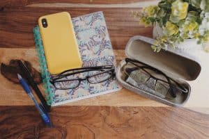 Two pairs of blue light blocking glasses, by a phone, planner, plant, and pens