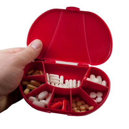 Red vita carry, vitacarry, pill case, pill box, vitamin box, vitamin organizer in hand with pills