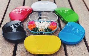 show different colors of the vitacarry container that holds a pill