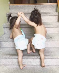 the twins holding hands as they walk upstairs